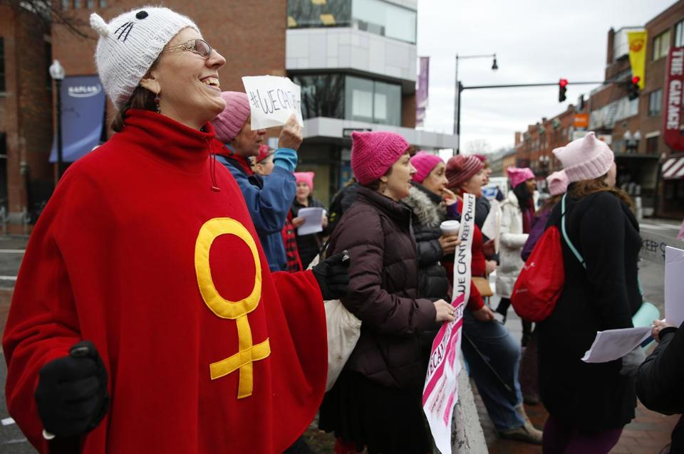 Teresa Tapper, 60, of Stoughton (left) sang along with other women gathered in Harvard Square.